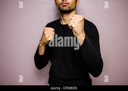 Young man raising his fists in preparation to fight - Stock Photo