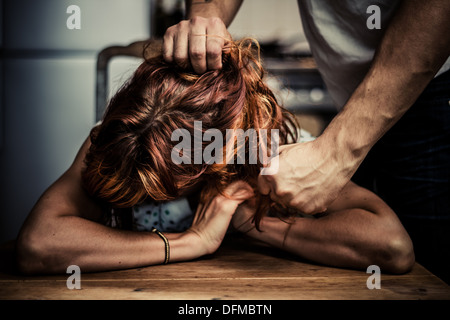 Man pulling the hair of his wife and threatening to punch her - Stock Photo