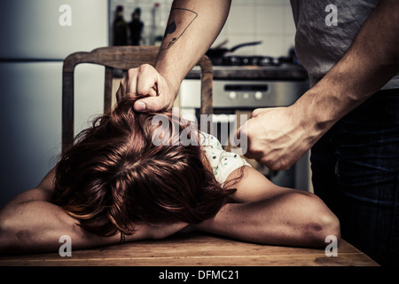 Man pulling his wife's hair in kitchen - Stock Photo