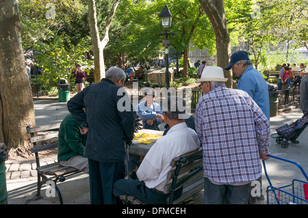 Senior Asian men playing Chinese Chess in Columbus Park in Chinatown in NYC (Xiangqi) - Stock Photo