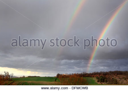 Double rainbow over hilly woodland and farmland in South West France - Stock Photo