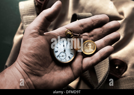 World War 1 One Soldier's hand holding pocket watch showing 11 am 11 o clock with locket showing a picture of his - Stock Photo