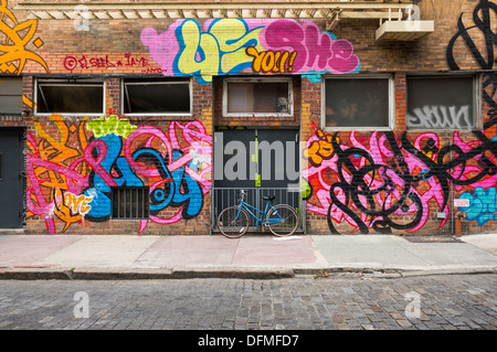 Bicycle resting against graffiti covered building in NYC - Stock Photo