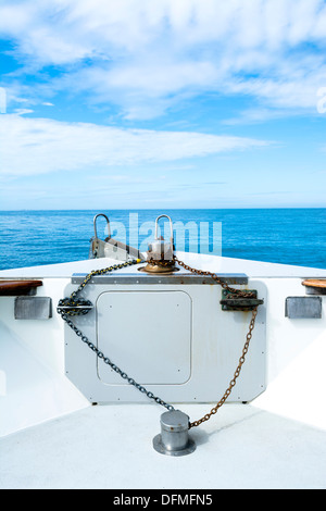The bow of a passenger cruise boat shows its rusty anchor chain, cleats and winch amongst a blue sky and distant - Stock Photo