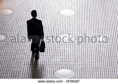 silhouetted business man with briefcase walking alone - Stock Photo