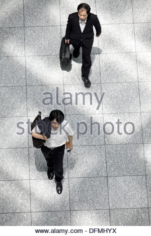 overhead view of business people walking with light from roof pattern on the floor - Stock Photo