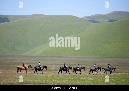 horsemen riding in open space, landscape, castelluccio di norcia, umbria, italy, europe - Stock Photo