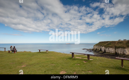 A couple looking over Thornwick Bay from Thornwick Nab - Stock Photo
