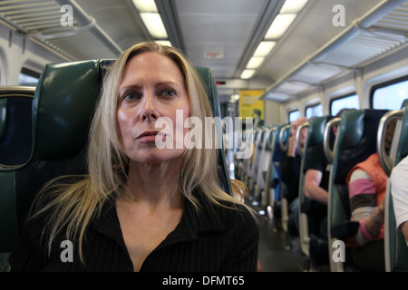 Woman daydreaming on a commuter train from the suburbs into New York City, New York, USA - Stock Photo