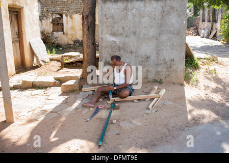 Indian man doing carpentry outside his home in a rural indian village. Andhra Pradesh, India - Stock Photo