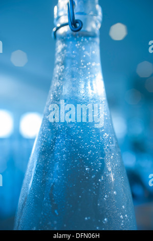 Water condensing on a bottle of cold water in a restaurant. - Stock Photo