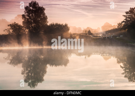 Early morning mist at Caen Hill Locks on the Kennet and Avon Canal in Devizes, Wiltshire. - Stock Photo