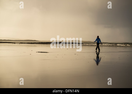Reflection of woman walking on Traigh Lingeigh beach, North Uist, Outer Hebrides, Scotland - Stock Photo