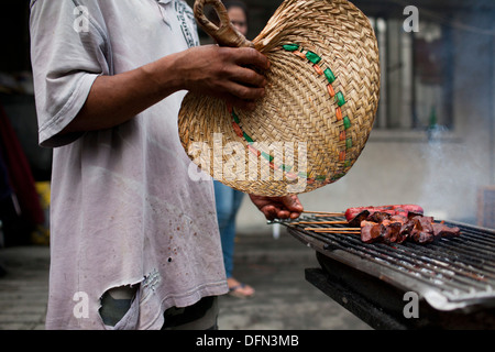 A street vendor cooks skewered chicken parts on a charcoal grill in Baclaran, Manila, Philippines. - Stock Photo