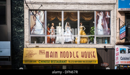 Mannequins displaying wedding dresses in the window of a retailer in New York - Stock Photo