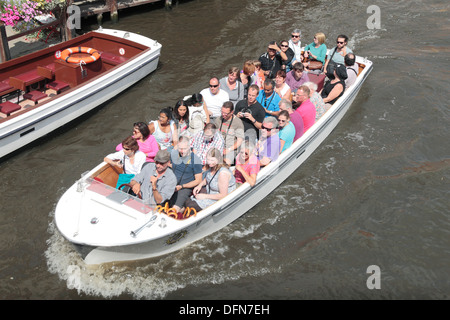 A full to the brim tourist boat on the canal in the beautiful city of Bruges (Brugge), Belgium. - Stock Photo