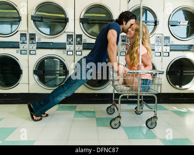 A young man leans over a pretty woman sits on a wheeled basket to kisses her chick in San Diego coin laundromat. - Stock Photo