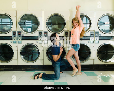 A smart young man kneels down before a beautiful woman in San Diego coin laundromat. - Stock Photo