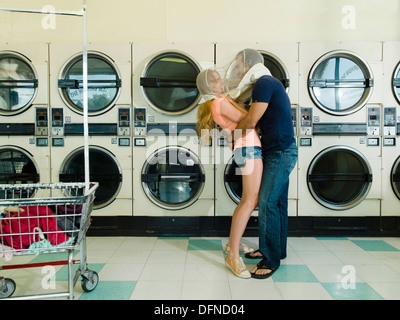 A pretty woman hugs by a smart young man in San Diego coin laundromat. - Stock Photo