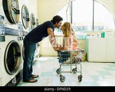 A young man leans over to feel the nose of a beautiful lady who sits on wheeled basket in San Diego coin laundromat.