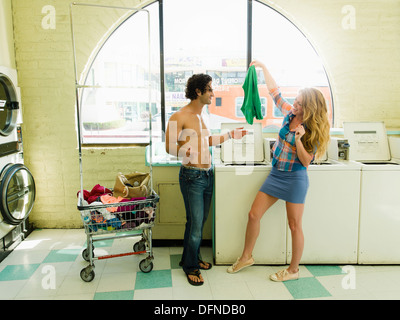 A pretty woman hangs a T-shirt before a bared body young man in San Diego coin laundromat. - Stock Photo