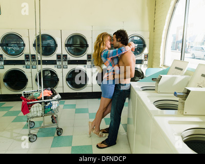 A pretty woman hugs a bared body young man in San Diego coin laundromat. - Stock Photo