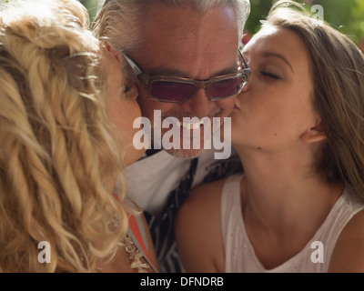 Two beautiful ladies kiss on both the chicks of a middle aged man in San Diego. - Stock Photo