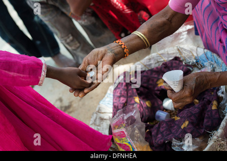 Young Indian girl paying for a cone of peanuts in a rural indian village. Andhra Pradesh, India - Stock Photo