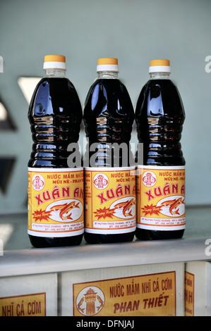 Bottles of vietnamese fish sauce, Mui Ne fishing village, Vietnam - Stock Photo