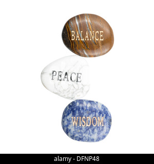 Stones with the words Balance (Polished Tiger Iron), Peace (Howlite), and Wisdom (sodalite). - Stock Photo