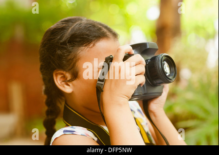Girl photographing with a digital camera - Stock Photo