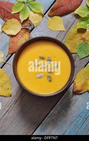 Bowl of pumpkin soup on rustic wooden table.