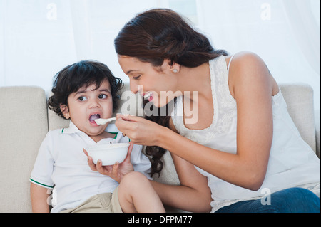 Woman feeding baby food to her son - Stock Photo