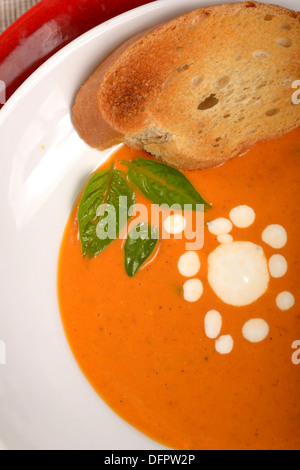 Delicious bowl of homemade tomato soup with grilled bread, basil and sour cream - Stock Photo