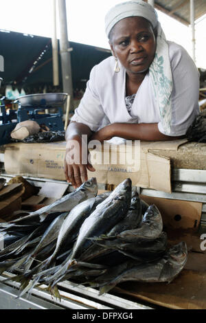 Afrian woman in white clothes, leaning over the counter and selling her fish at the colonial style Mercado Central, - Stock Photo