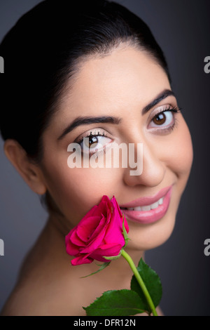 Portrait of a beautiful woman with rose - Stock Photo
