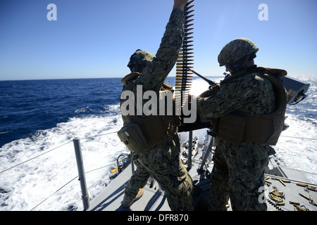 Sailors assigned to Coastal Riverine Squadron (CRS) 2 load ammunition into a remotely operated .50 caliber machine - Stock Photo