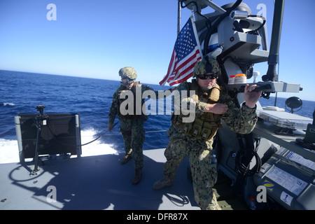 Sailors assigned to Coastal Riverine Squadron (CRS) 2 observe a live-fire exercise aboard a Coastal Command Patrol - Stock Photo