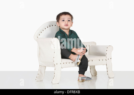 Portrait of a 5 year old indian boy seating on a sofa - Stock Photo