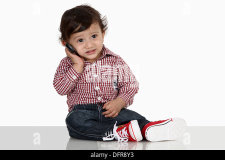 Four year old indian boy talking on a cell phone - Stock Photo