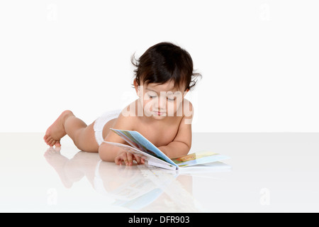 A 3 year old boy reading a book - Stock Photo