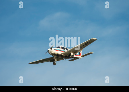 Light aircraft in Tayside Aviation colours flying overhead on a summer's day. - Stock Photo