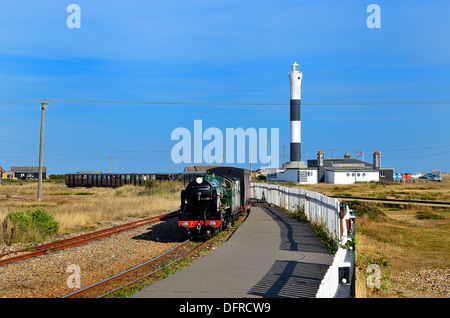 Dungeness lighthouse with steam train in foreground approaching station Dungeness, Kent, England, UK - Stock Photo