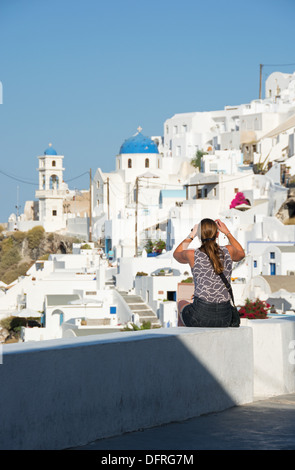 SANTORINI (THIRA), CYCLADES, GREECE. A holidaymaker photographing the picturesque cliff-top village of Imerovighli - Stock Photo