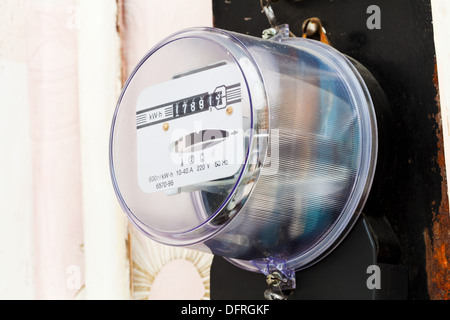 electricity supply meter on wall of living room - Stock Photo