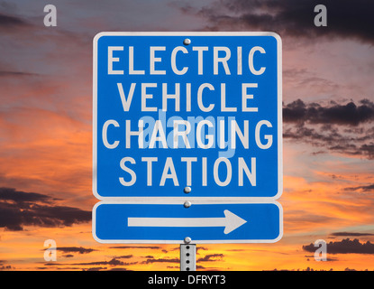 Electric vehicle charging station sign isolated with sunset sky. - Stock Photo