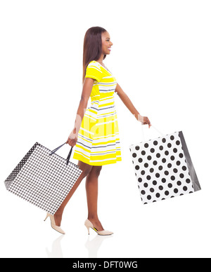 side view of happy afro American woman walking with shopping bags - Stock Photo