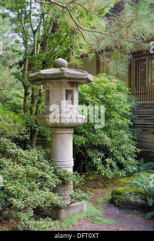 Japanese Stone Lantern in Garden with Trees Plants and Shrubs during Fall Season