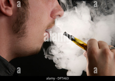Vaping - Man smoking an electronic cigarette and exhaling the smoke - Stock Photo