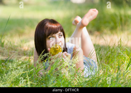 Lying on grass with a pear in her mouth - Stock Photo